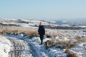 Margaret and Millie walking on Winter Hill moors in the snow